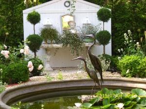 Vor Der Wand Schmücken Eine Büste, Verschiedenen Gefäße Mit Weißen Pflanzen  Und Ein Leuchter Den Davor Stehenden Steintisch.